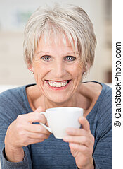Blond short-haired senior woman holding a cup - Vertical...