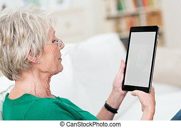 Senior lady relaxing reading an e-book
