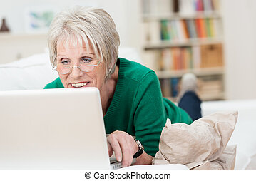 Tech savvy senior woman relaxing with a laptop at home lying...
