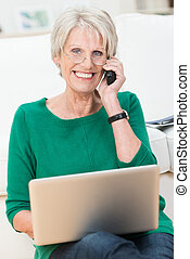 Delighted elderly woman chatting on a mobile