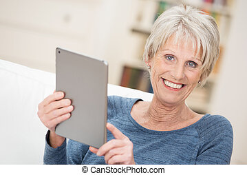 Happy senior woman holding a tablet computer in her hands as...