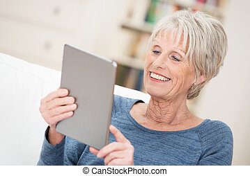 Elderly woman smiling as she reads her tablet - Elderly...
