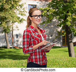 smiling girl in eyeglasses with tablet pc computer -...