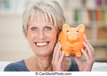 Excited senior woman holding up her piggy bank smiling in...