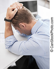 stressed businessman with papers at work