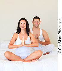 Young couple meditating in bed