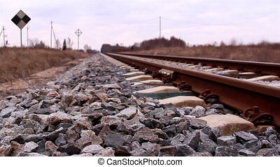 The metal railroads for trains with lots of stones on the...