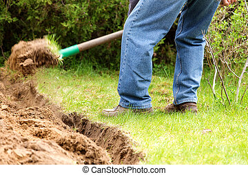 A man digging in the garden soil. - Home gardening in the...