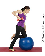 Young woman working out with a pilates ball and a dumbbell -...