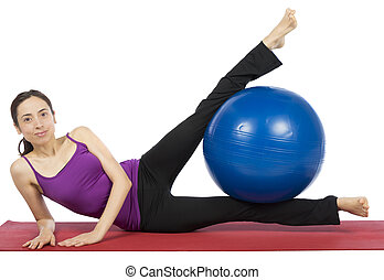 Fitness woman exercising her legs with a pilates ball -...