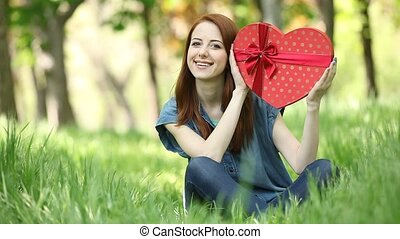Young girl with shape heart in the park