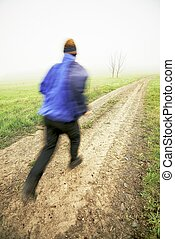 Man running on a dirt road with trees and mist in the...