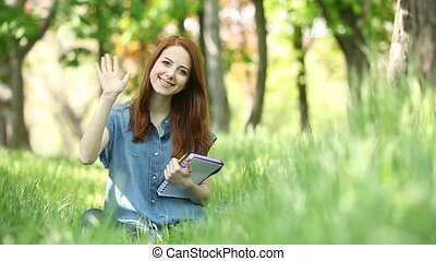 Young redhead smiling woman with notebook in the city park.