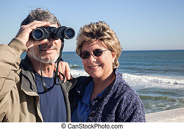 Retired couple on beach vacation with Binoculars - Happy...