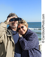 Retired couple on beach vacation with Binoculars hugging -...