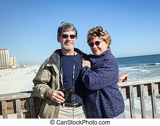 Happy Retired Couple on Fishing Pier at Sunny Beach - Happy...