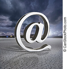 At symbol in a dry lake bed with stormy clouds