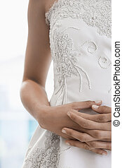 Bride's hands on stomach (focus on hands)