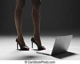 Businesswomans legs by laptop computer low section