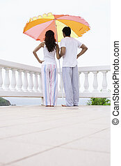 Young couple standing under parasol and looking at view