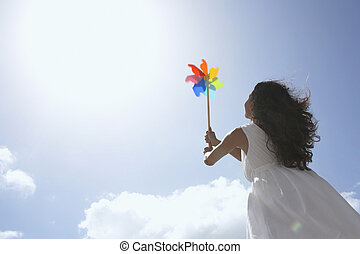 Young woman with pinwheel against sky (low angle view)