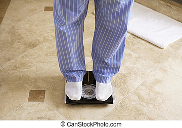 Mature man on bathroom scale low section