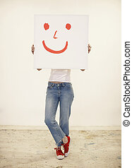 Young woman holding drawing of smiley face