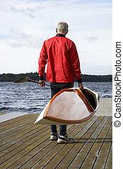 Senior man holding a kayak