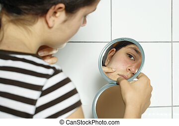 Checking her blemishes - Young teenage female holding a...