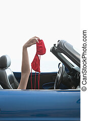 Mid-Adult Woman Holding Bikinis in Convertible