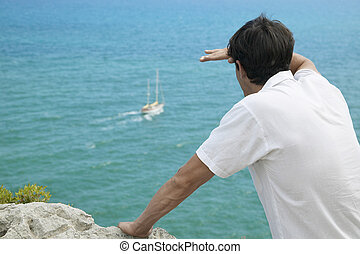 Mid-Adult Man Looking at Boat in Sea