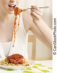 Midsection of Young Woman Eating Spaghetti