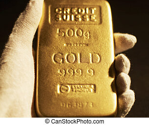 Woman's Hand Holding Gold Bar