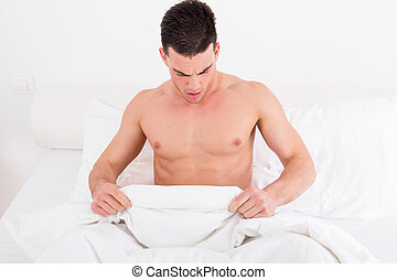 half naked young man in bed looking down at his underwear -...