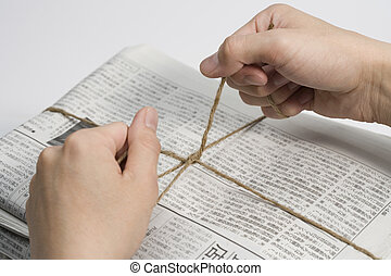 hand of person binding old newspapers with strings