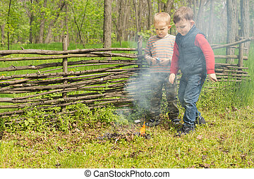 Proud little boys standing watching a burning fire that they...
