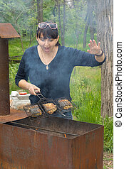 Woman cooking on a BBQ calling out