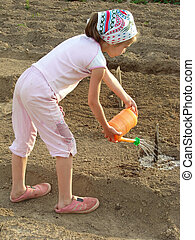 watering - little girl watering vegetable bed at the rural...
