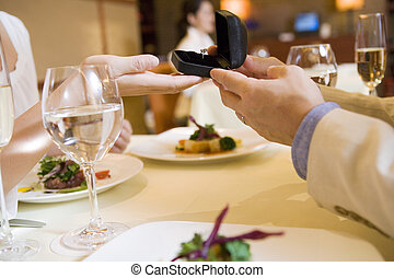 man giving woman a ring at restaurant