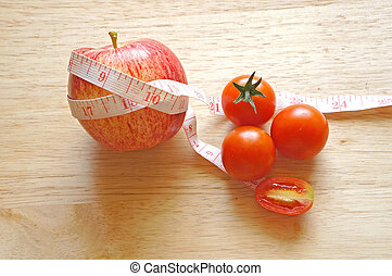red apple wrapping with tape measure and tomatoes (diet concept)