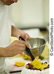 Patissier finishing decoration of fruits for cake