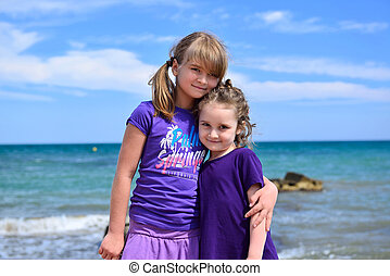 Two sisters posing on the beach - Two little sisters posing...