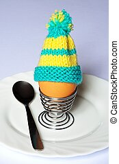 Boiled egg with an egg cosy. - Boiled egg in a coiled metal...