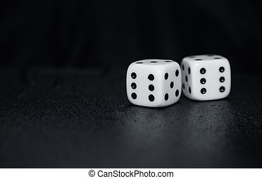 Gambling dices - Two gambling dices on a dark table