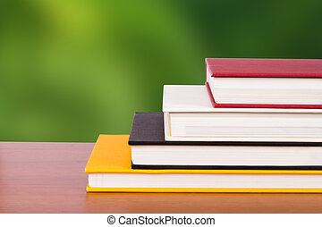 Book Covers - Books with covers on wooden table, side view...