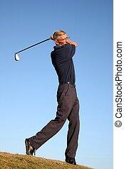 Fairway Golf Stroke - Senior golfer playing a stroke on the...