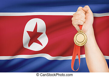 Medal in hand with flag on background - Democratic Peoples...