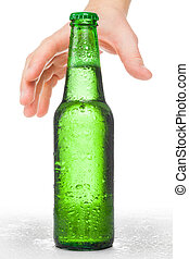 Male hand trying to reach bottle of beer - studio shot over...
