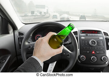 Man holding bottle of beer while driving car - Man hand...