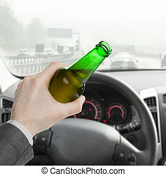 Man holding bottle of beer in his left hand while driving...